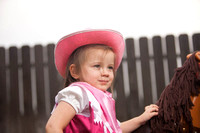 Portrait of Girl Dressed as a Cowgirl Next to a Toy Horse