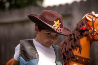 Boy Dressed as a Cowboy Standing Next to Toy Horse