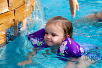 Little Girl with Floaties Swimming in Pool
