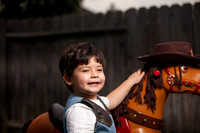 Boy Dressed as a Cowboy Putting Hat on Toy Horse