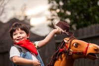 Portrait of Boy Dressed as a Cowboy Riding a Toy Horse