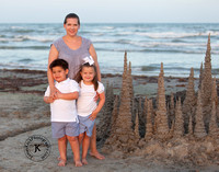 Mother, Son, and Daughter Portrait on the Beach with Sand Castle