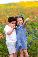 Portrait of Brother and Sister Blowing Kisses in Wildflowers