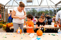 Kids working on decorating pumpkins