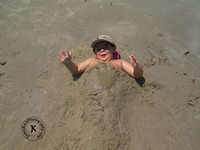 Little Boy Covered in Sand on the Beach
