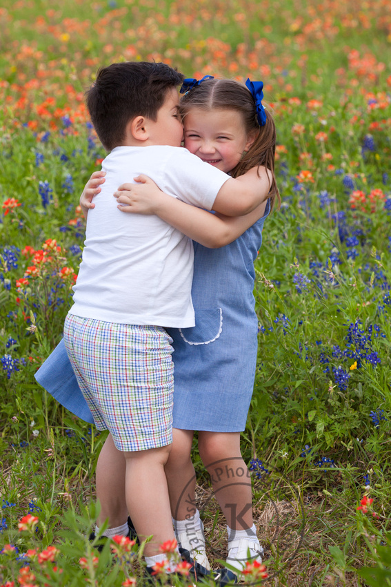 Portrait of Brother and Sister Hugging in Wildflowers