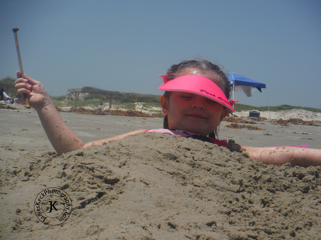 Little Girl Covered in Sand on the Beach