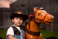 Boy Dressed as Cowboy Standing Next to Toy Horse