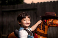 Boy Dressed as Cowboy Putting Hat on Toy Horse